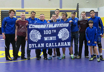 wrestlers stand with 100th winner banner