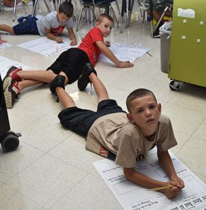 3 students writing on posters on floor