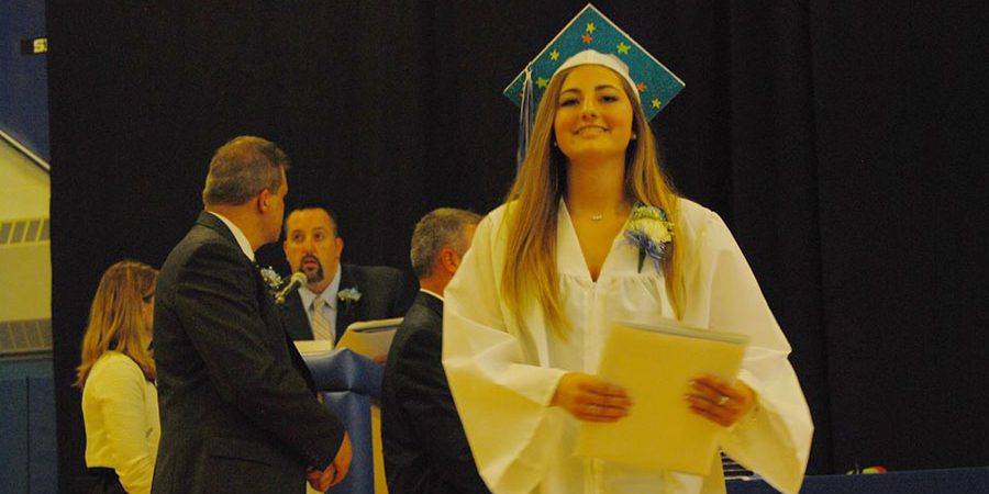 girl walks off stage carrying her diploma and smiling