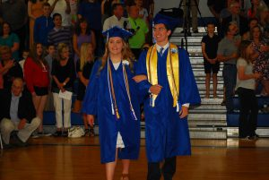 a male and a female walk into graduation arm in arm