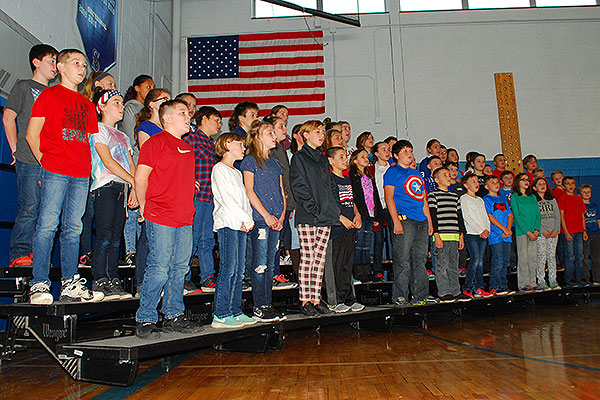 students stand in row in front of American flag