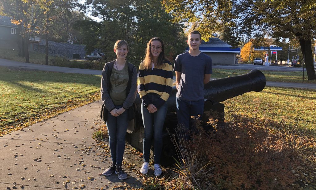 Three students stand in front of a cannon