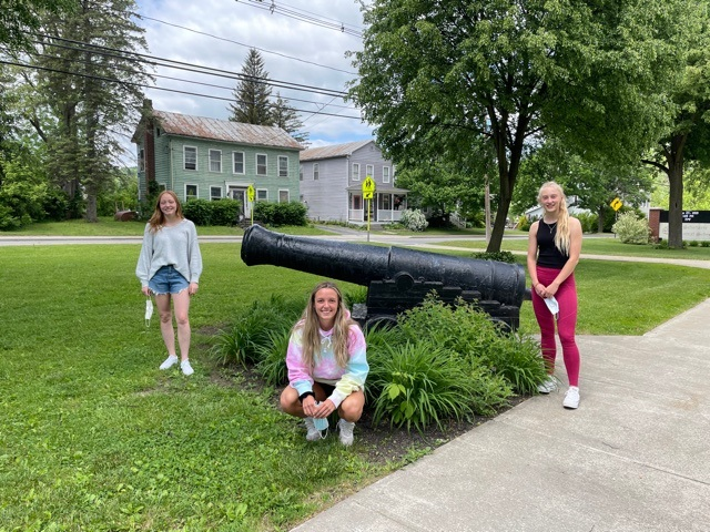 three students stand near cannon