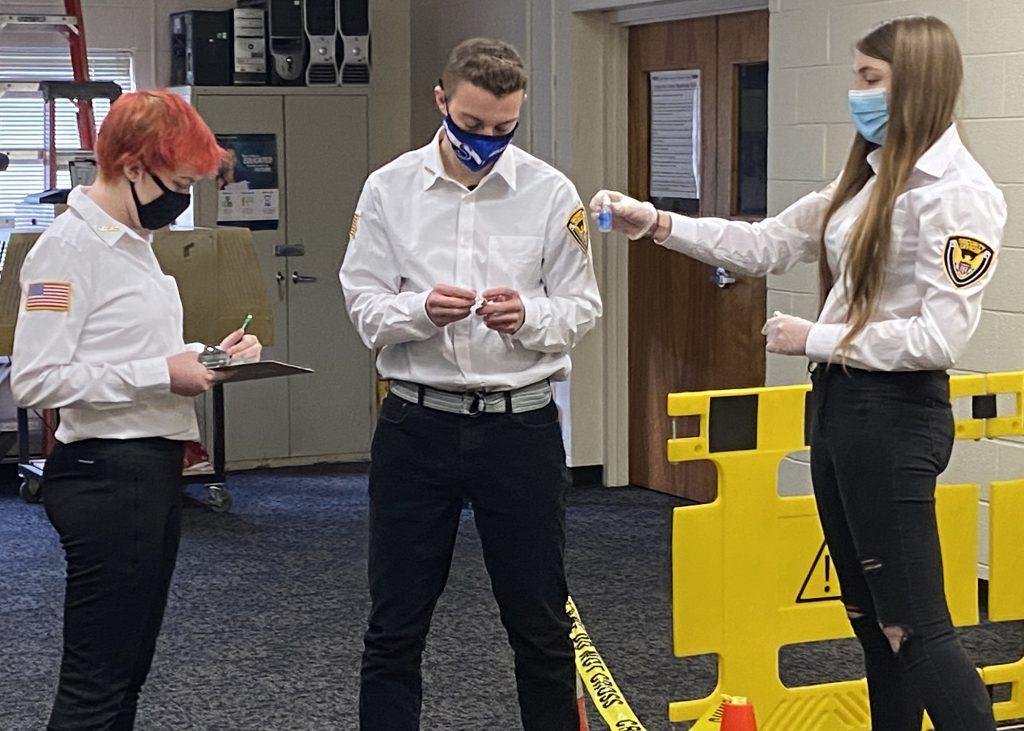 Three students process a fake crime scene