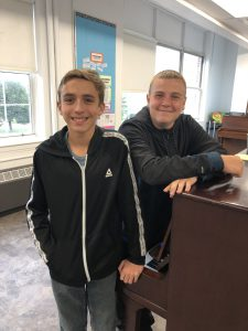 Two students stand next to piano