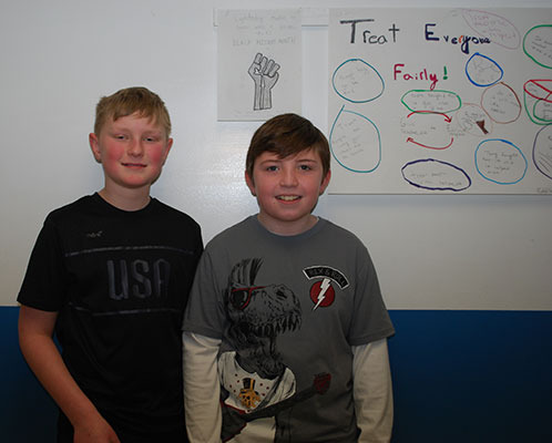 2 students stand in front of posters they created