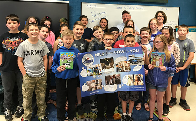 5th graders and teachers and Commissioner Ball pose as a group with dairy poster