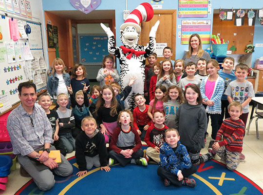 students sit on floor in front of Cat in the Hat