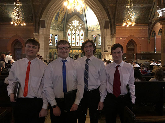 4 young men standing inside Sage Chapel
