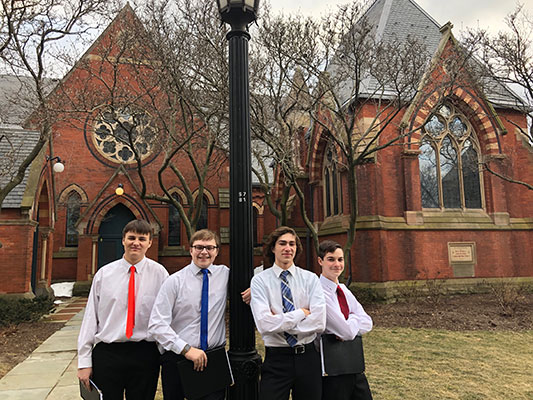 4 young men standing in front of Sage Chapel