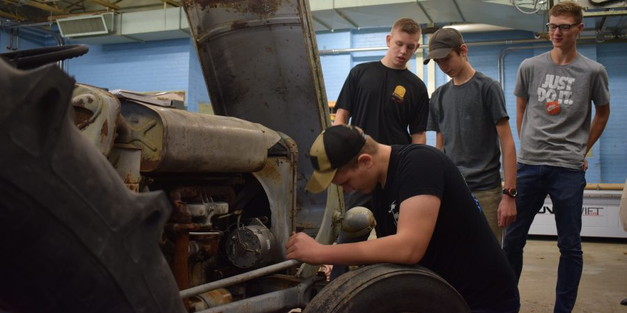 Four students work on a tractor