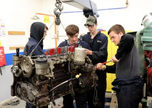 Four students work on a motor