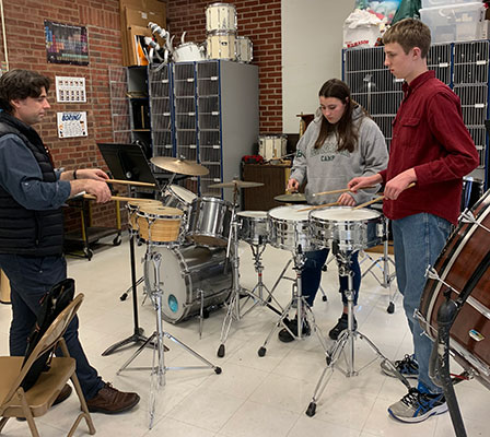 adult teaching 2 students on snare drums