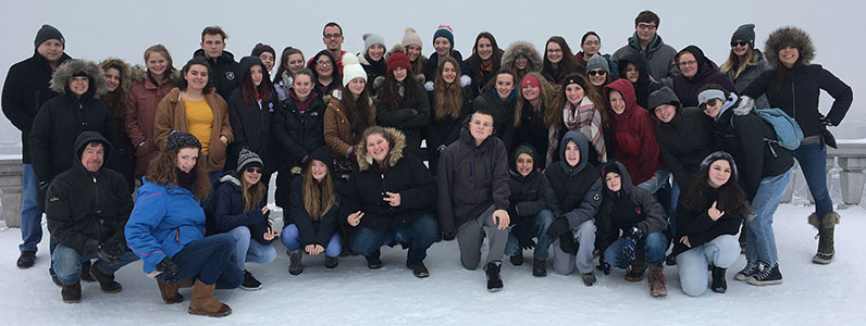 group of 40 students and teacher pose together in the snow