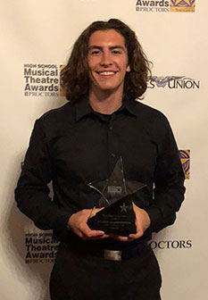 male student actor holds award trophy