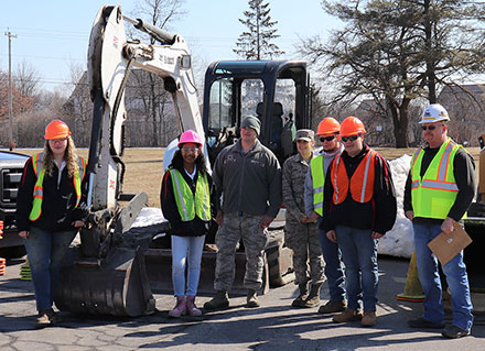 group of students and instructor standing in front of heavy equipment