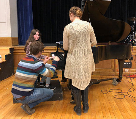 2 adults instruct student seated at piano