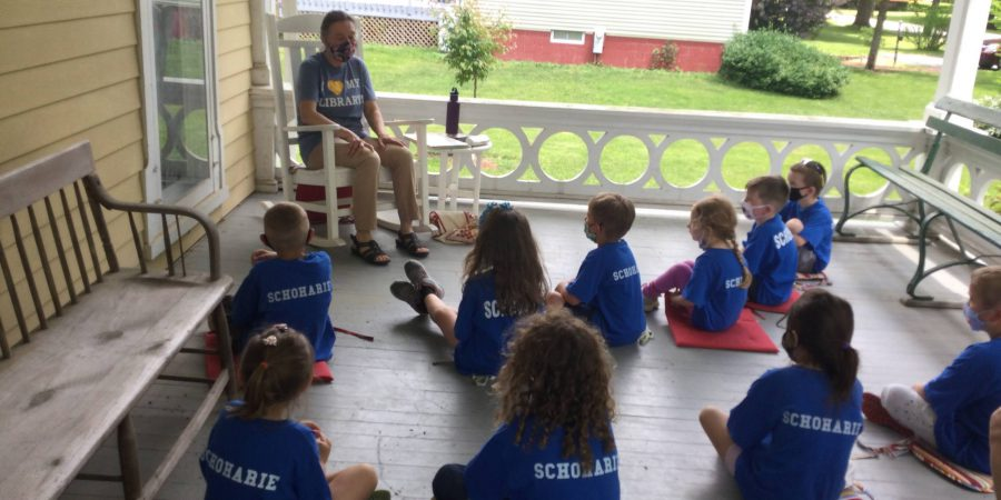 Seated students are read to by an adult