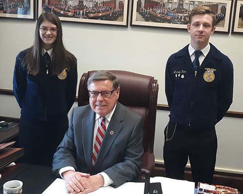 Jamie and Andrew stand behind seated Senator Seward