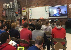 students listen as Philip Klein talks via a smart board screen