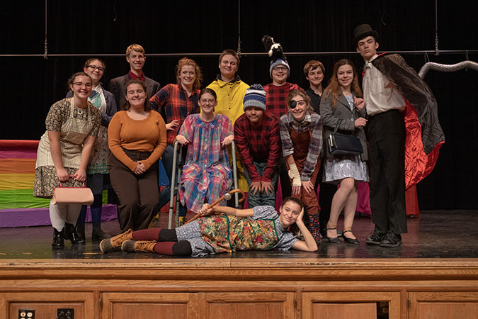 group of student actors in costume on stage