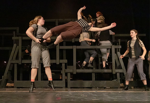 2 Newsies dancing, one flipping in the air
