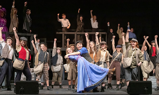 Newsies performers dancing and raising fists