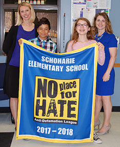students and teacher holding no hate banner