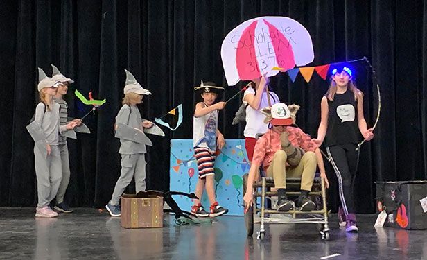 students in costume performing skit on stage