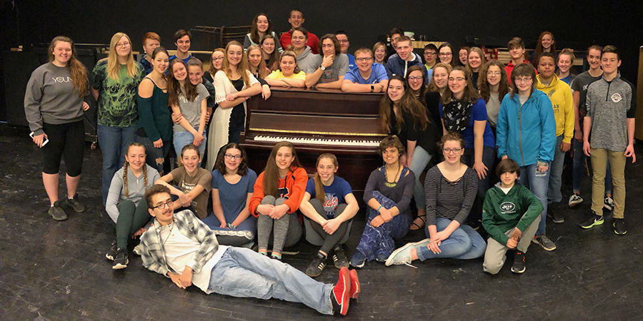 high school choir members gather around new piano