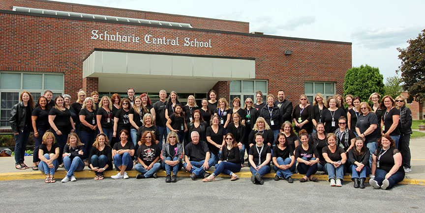 SCS faculty, staff, administration wearing black tops and blue jeans pose as a group