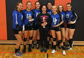 girls volleyball team stands with trophy