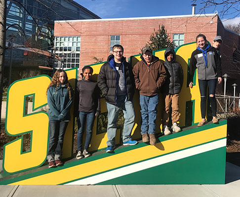 group of students stand in front of Siena sign