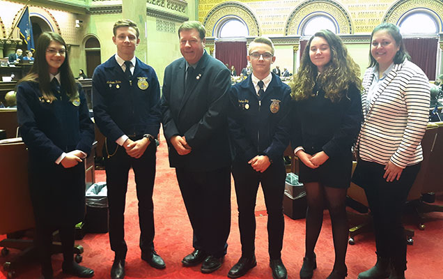 5 FFA members stand with Assemblyman Tague in Assembly chamber