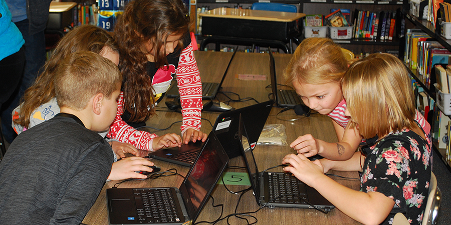 boys and girls working on laptops