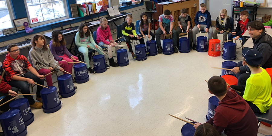 students drumming on buckets