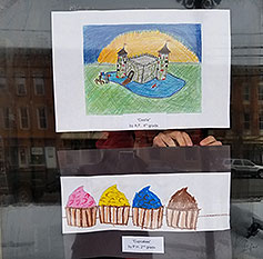 two piece of student art hang in a window