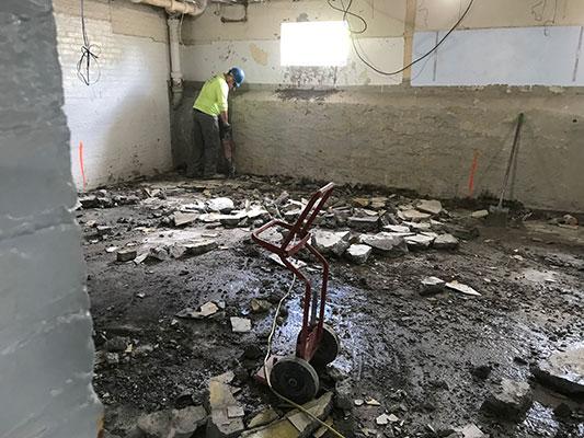 worker in a gutted room in basement