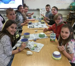A table of eight students work on bowls