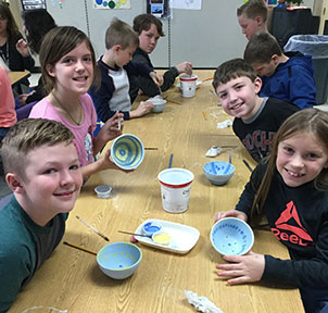 group of student show their painted bowls