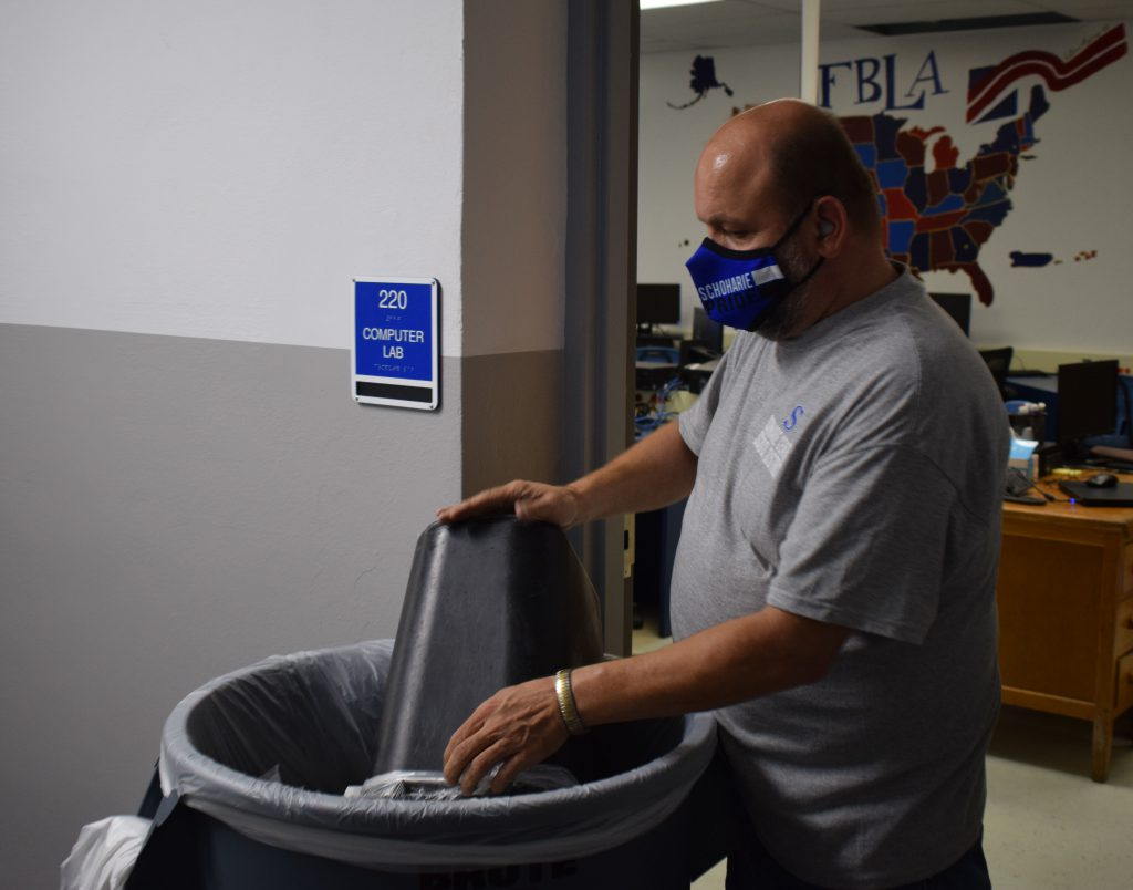 A man empties a garbage can