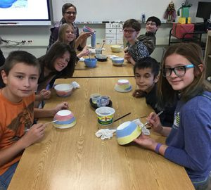students at tables painting bowls