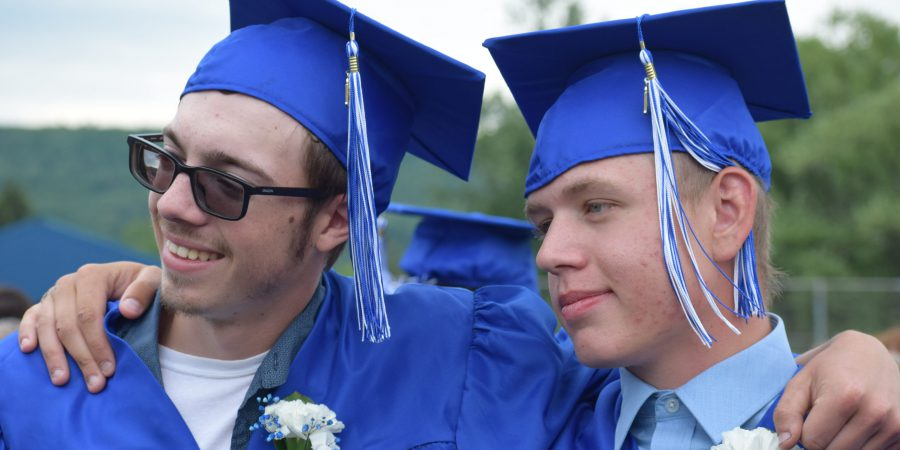 Two graduates pose for a photo