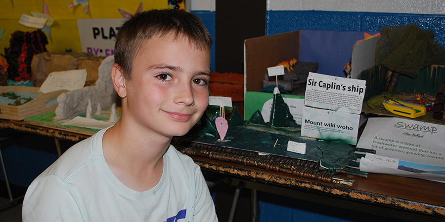 male student poses next to his landform display
