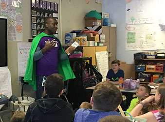 man dressed in spandex and a cape talk to young students