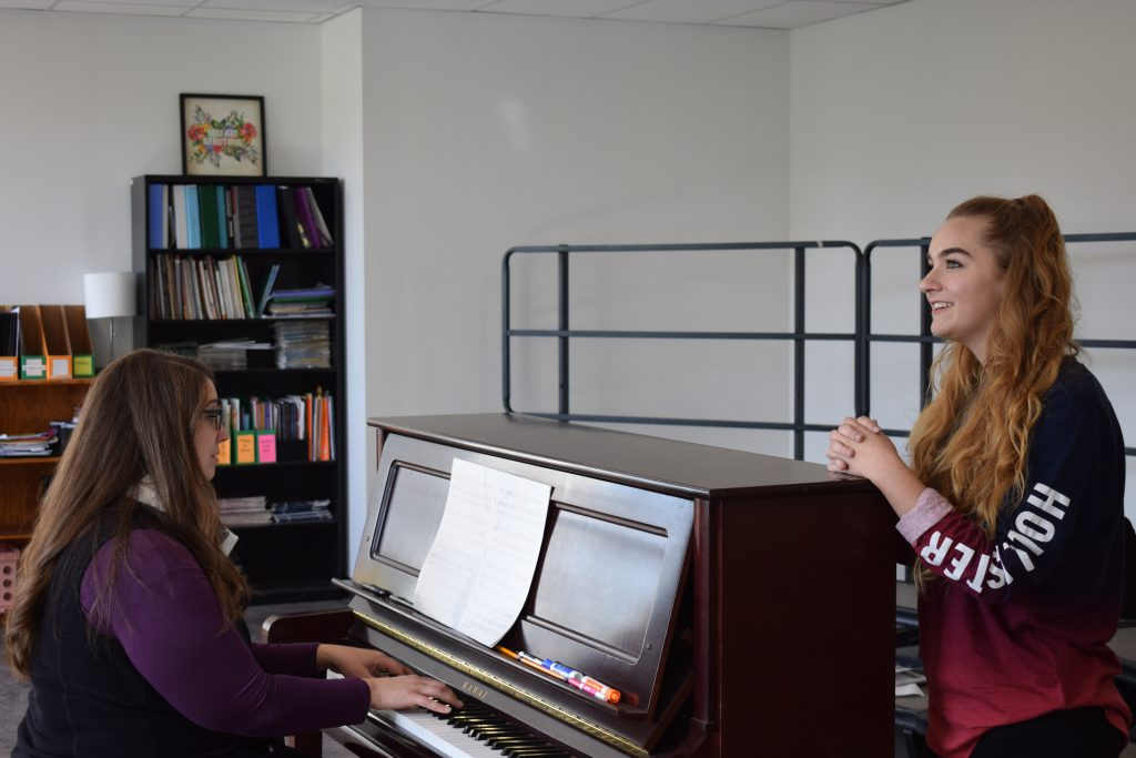 A teacher plays piano, and a student sings