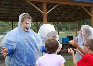 students push pies into teachers' faces