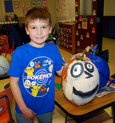 boy standing next to pumpkin