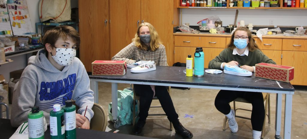 Three students work at a table