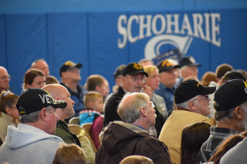 Two dozen veterans sit in chairs